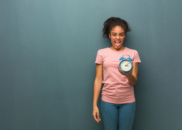 Молодая негритянка смешная и дружелюбная показывающая язык. она держит будильник.