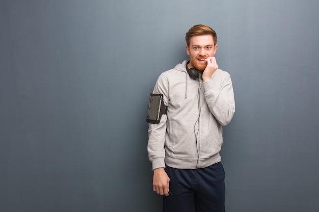 若いフィットネス赤毛の男が爪をかむ、神経質で非常に不安