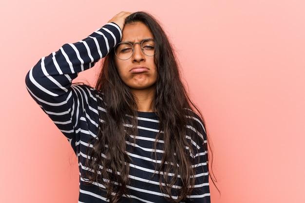 若い知的なインドの女性は疲れて非常に眠い彼の頭に手を維持します。