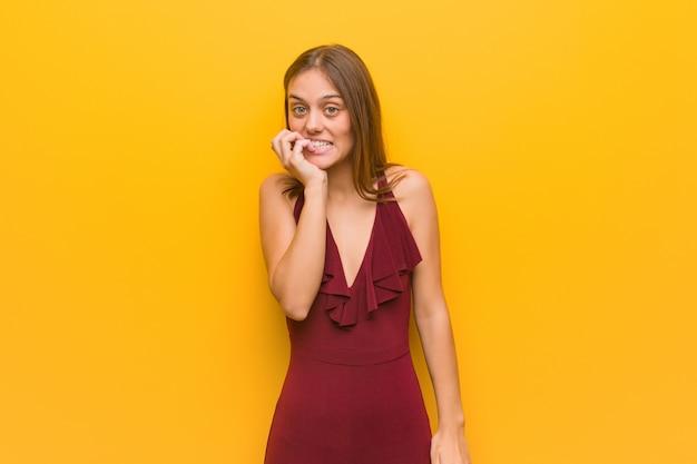 爪をかむ神経質で非常に不安なドレスを着ている若いエレガントな女性