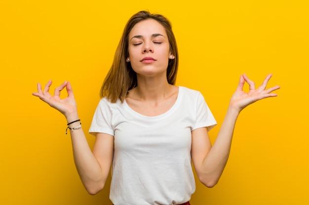 Молодая естественная кавказская женщина ослабляет после тяжелого рабочего дня, она выполняет йогу.