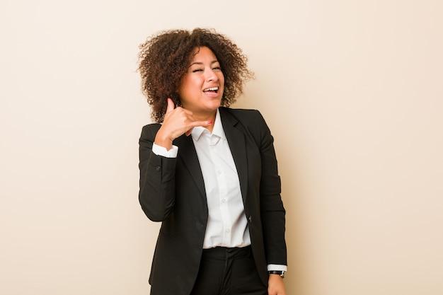 指で携帯電話のジェスチャーを示す若いビジネス女性。