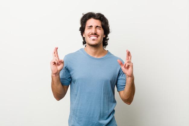 運を持っていることのための指を交差する白い背景に対して若いハンサムな男