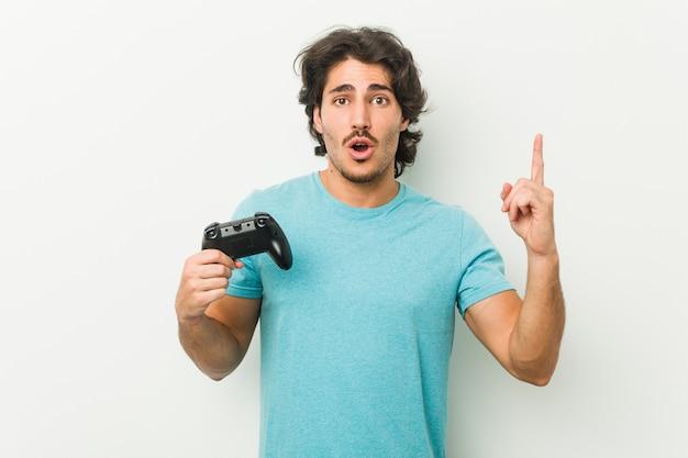 いくつかの素晴らしいアイデア、創造性の概念を持つゲームコントローラーを保持している若い男。