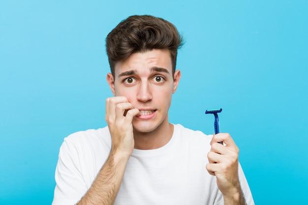 爪をかむかみそりの刃を保持している若い白人男、神経質で非常に心配しています。