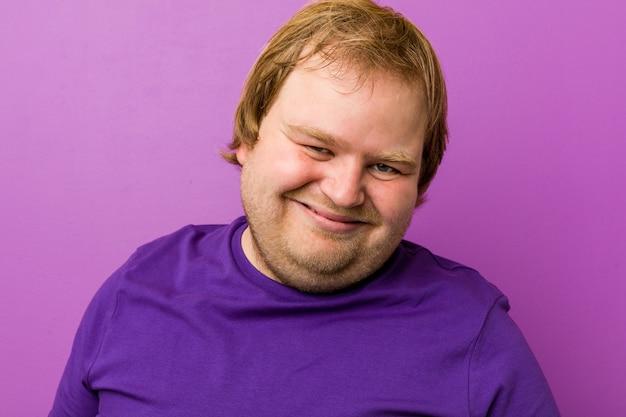 若い本物の赤毛のデブ男は笑って目を閉じ、リラックスして幸せを感じます。