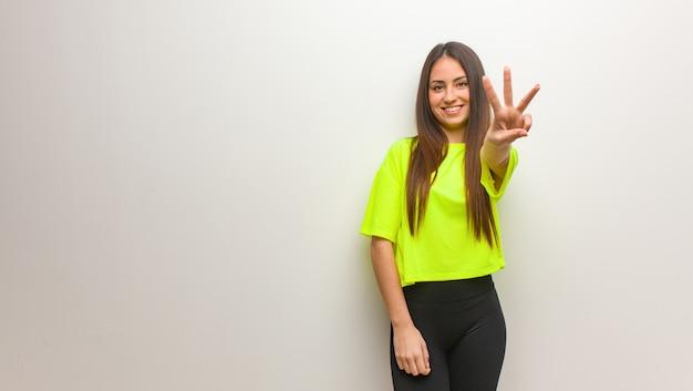 Молодая современная женщина показывает номер три