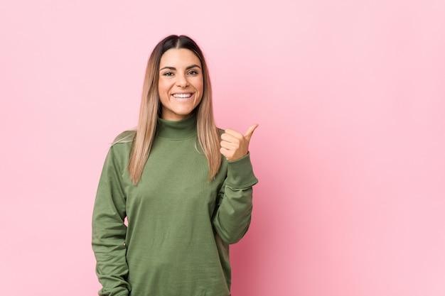 Молодая кавказская женщина изолировала усмехаться и поднимать большой палец руки вверх