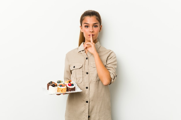 秘密を守るか沈黙を求める甘いケーキを保持している若い白人女性。
