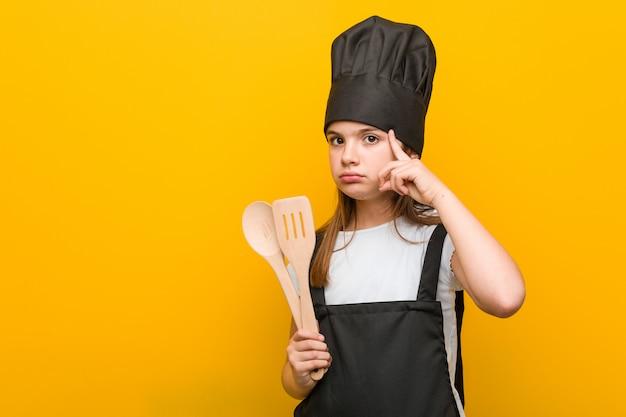 Маленькая кавказская девушка нося костюм шеф-повара указывая его висок с пальцем, думая, сфокусированный на задаче.