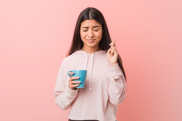 Молодая арабская женщина держит чашку скрещивания пальцев за удачу
