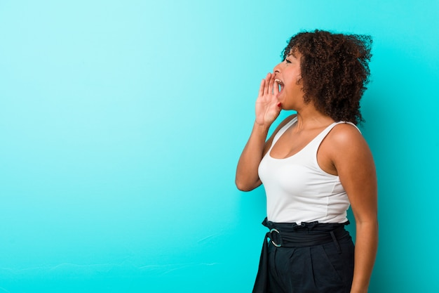 若いアフリカ系アメリカ人女性の叫びと開いた口の近くの手のひらを保持しています。