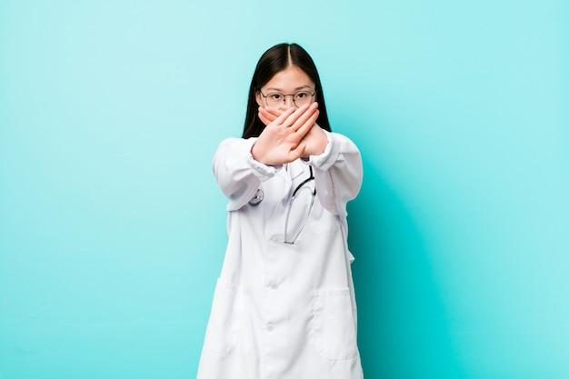 拒否ジェスチャーを行う若い中国医師女性