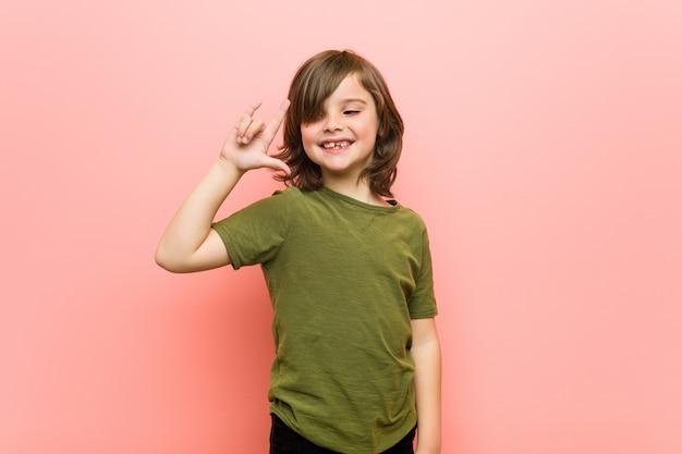 革命の概念として角ジェスチャーを示す小さな男の子。
