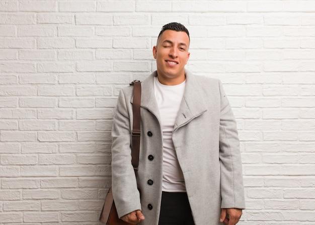 Молодой латинский деловой человек подмигивает, веселый, дружелюбный и беззаботный жест
