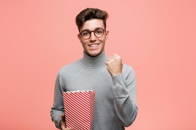 勝利または成功を祝うポップコーンバケツを持って若い知的な男