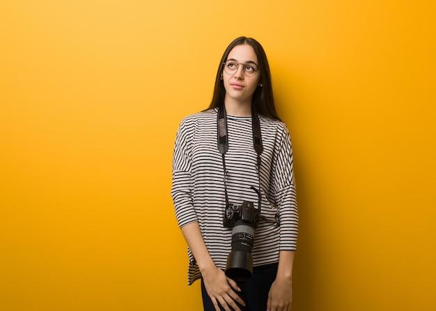 Молодой фотограф женщина мечтает о достижении целей и задач
