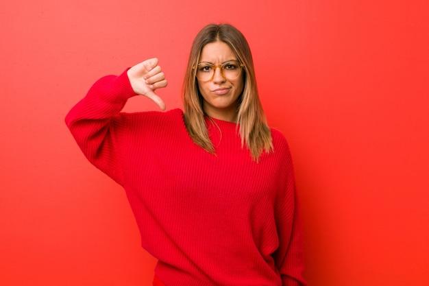 嫌いなジェスチャーを示す壁に対して若い本物のカリスマ的な本物の女性は、親指を下げます。不一致の概念。