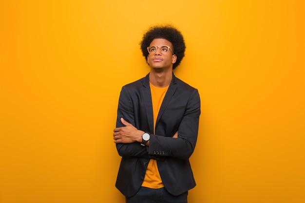 オレンジ色の壁の上の若いビジネスアフリカ系アメリカ人男性が疲れて、退屈