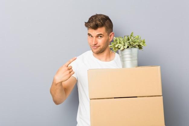 Молодой человек делает движение, держа коробки, указывая пальцем на вас, как будто приглашая подойти ближе.
