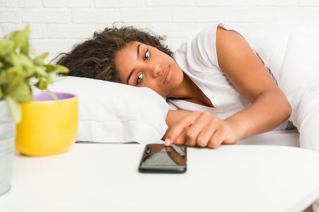 Заделывают молодой афро-американской женщины, лежа на кровати, глядя на телефон