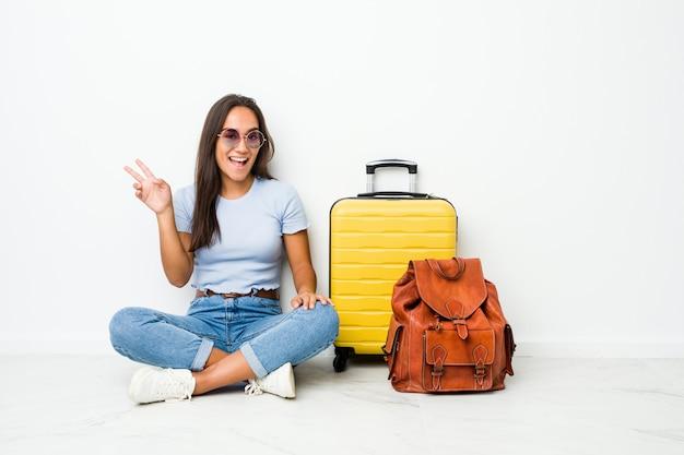 指で平和のシンボルを見せてうれしそうな屈託のない旅行に行く準備ができている若い混血インドの女性。