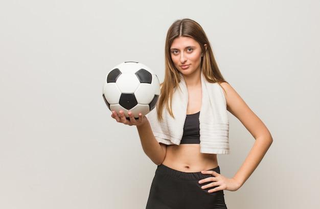 まっすぐ見ている若いフィットネスロシア女性。サッカーボールを保持しています。