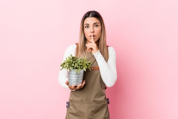 秘密を守るか沈黙を求める植物を保持している若い庭師の女性。