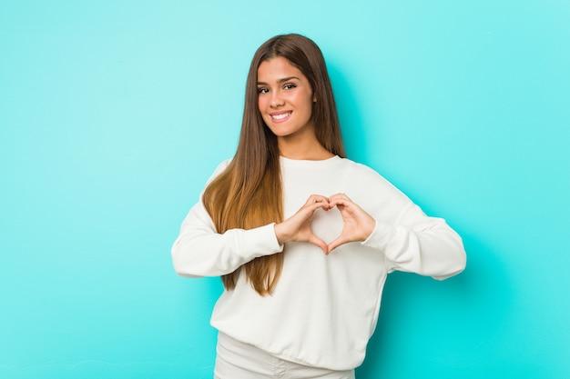 若いスリムな女性の笑みを浮かべて、手でハートの形を示します。