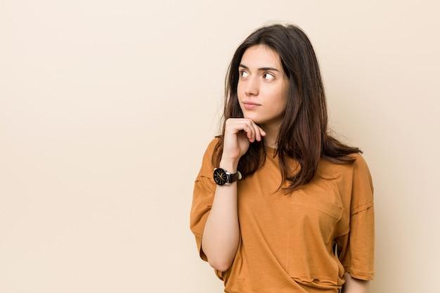 疑わしいと懐疑的な表情で横向きのベージュに対して若いブルネットの女性。