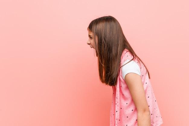 Милая маленькая девочка кричит в направлении копирования пространство