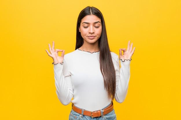 Молодая милая арабская женщина против желтого цвета ослабляет после тяжелого рабочего дня, она выполняет йогу.