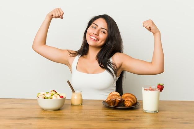 Молодая соблазнительная женщина, принимая завтрак, показывая силу жест с оружием, символ женской силы
