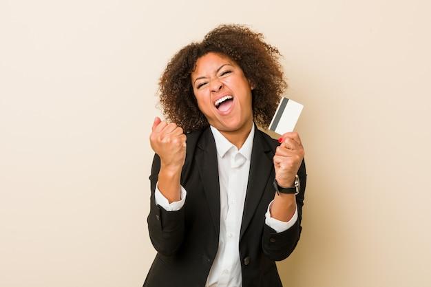 屈託のない、興奮して応援クレジットカードを保持している若いアフリカ系アメリカ人女性。勝利のコンセプト。