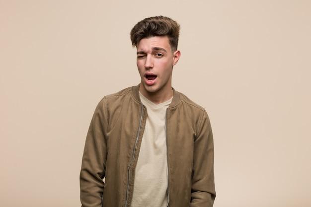 Молодой человек кавказской носить коричневый пиджак подмигивая, смешно, дружелюбно и беззаботно.