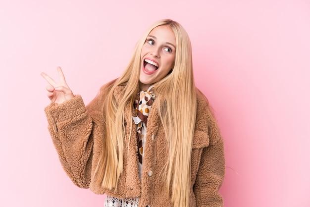 指で平和のシンボルを示すうれしそうな屈託のないピンクに対してコートを着ている若いブロンドの女性。