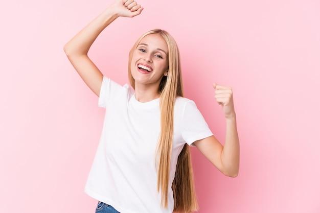Молодая блондинка на розовый, празднование особого дня, прыжки и поднять руки с энергией.
