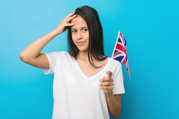 ショックを受けているイギリスの国旗を保持している若いヒスパニック系女性は、重要な会議を覚えています。