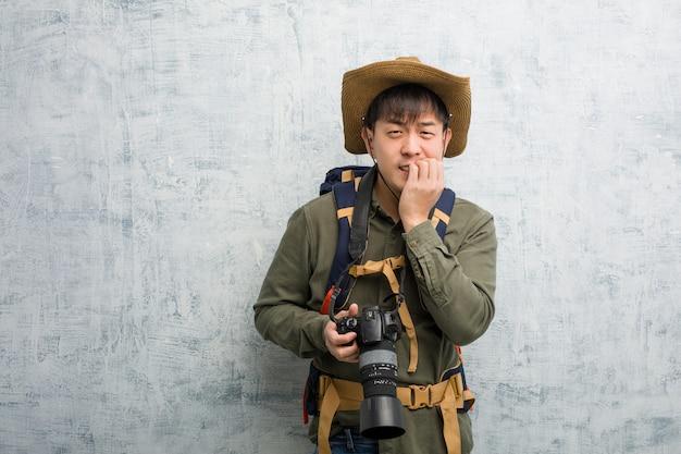 爪をかむカメラを保持している若い中国人探検家男、神経質で非常に不安