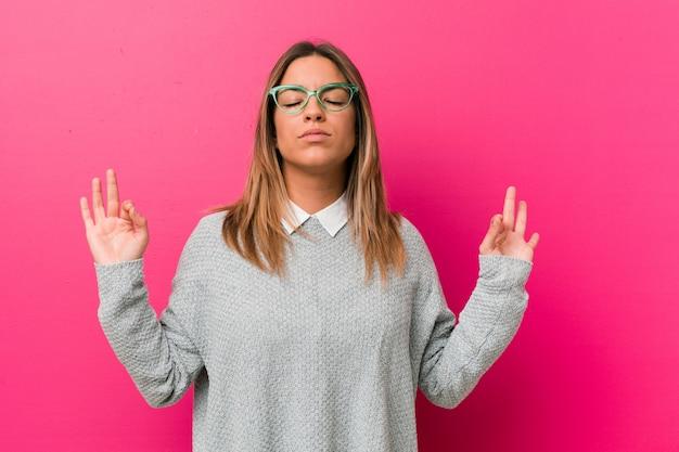 Молодая настоящая харизматичная женщина реальных людей у стены расслабляется после тяжелого рабочего дня, она выполняет йогу.