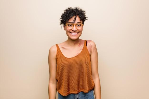 幸せ、笑顔、陽気な肌のあざを持つ若いアフリカ系アメリカ人女性。