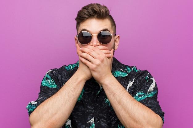 Молодой человек, одетый в отпуск смотреть шокирован охватывающих рот руками.