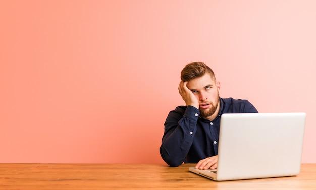 Молодой человек, работающий с его ноутбуком, который скучает, устал и нуждается в день отдыха.