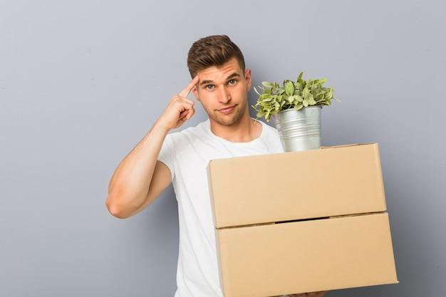 Молодой человек делая движение держа коробки указывая его висок с пальцем, думая, сфокусировал на задаче.