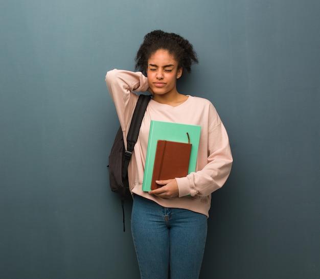 首の痛みに苦しんでいる若い学生黒人女性。彼女は本を持っています。