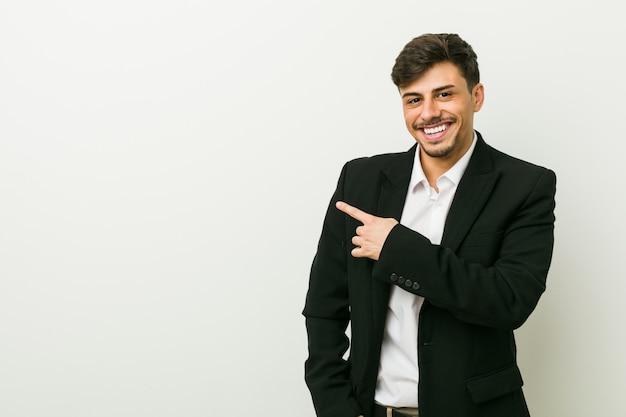 若いビジネスヒスパニック男笑顔とさておき、空白スペースで何かを示します。
