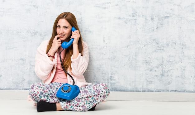 固定電話を保持している若い白人女性は、コピースペースを見て何かについて考えてリラックスしました。