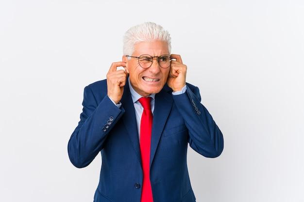 中年の白人ビジネスマンが手で耳を覆って分離しました。