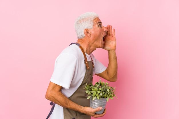 中年の庭師の男は、叫び、開いた口の近くの手のひらを保持を分離しました。