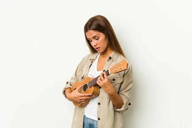 分離されたウクレレを演奏若い白人女性